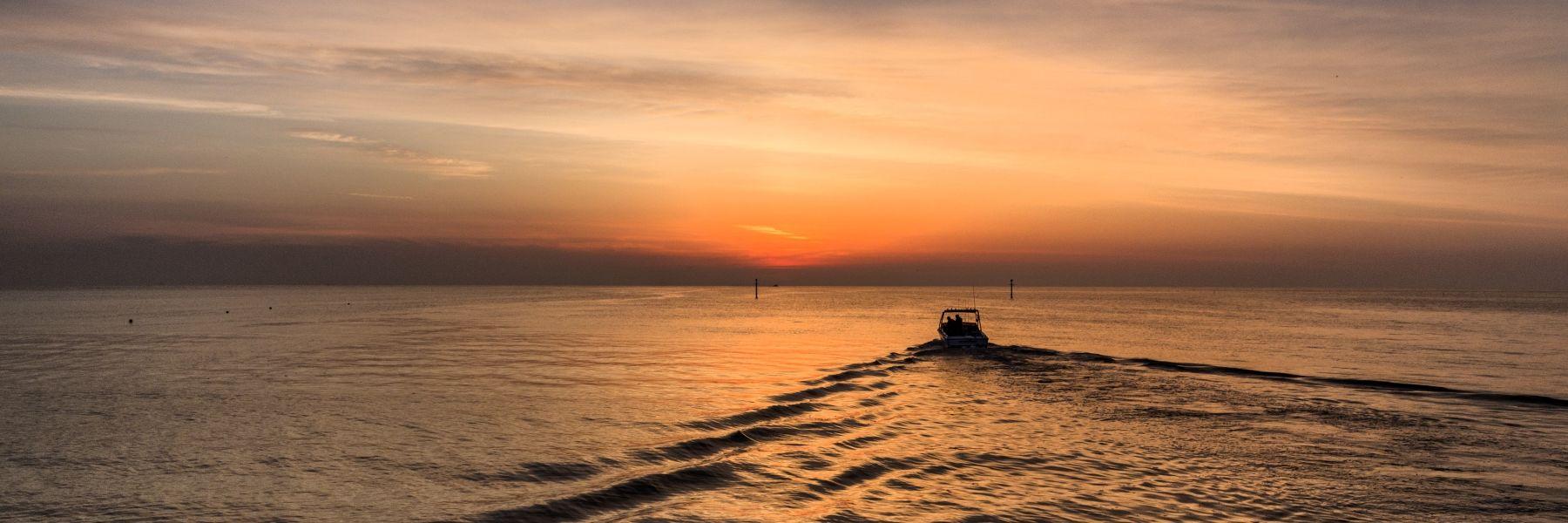 Un'alba in riva al mare con peschereccio - EN